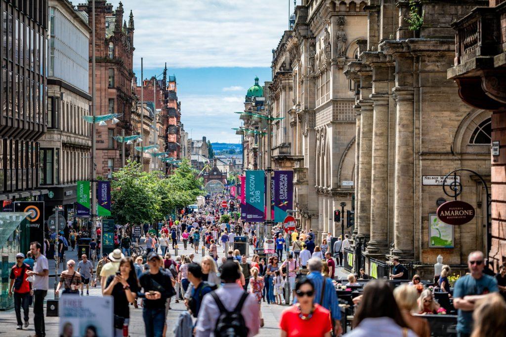 people walking between concrete buildings at daytime